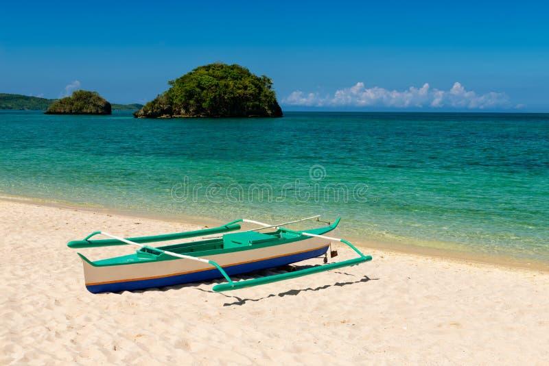 Fishboat na piasku i dwa małych wyspach na zwrotnika turkusu morzu obrazy stock