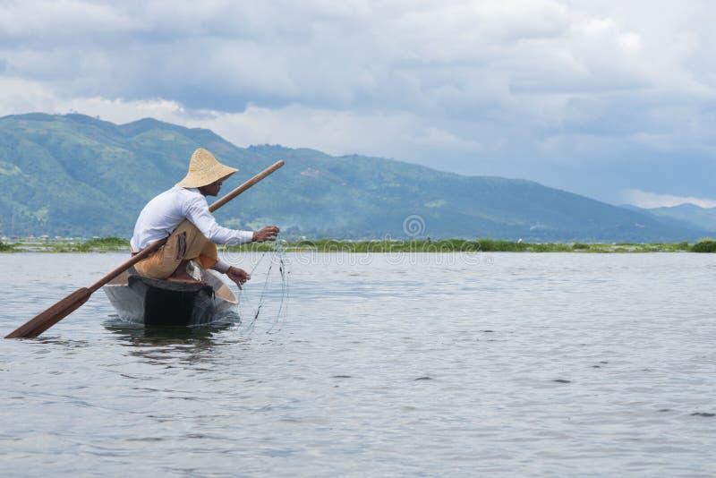 Fisheerman som fiskar ans som sitter på det lilla träfartyget på inlesjön i myanmar royaltyfria bilder
