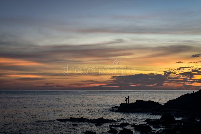 Fisher à la côte de falaise pendant le coucher du soleil photographie stock