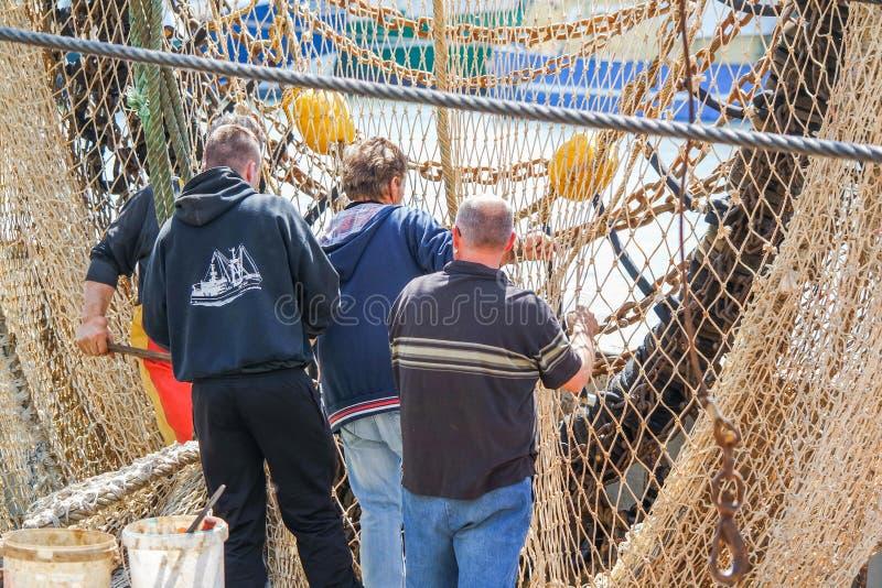 Fisher att reparera förtjänar, innan det lämnar hamnen arkivfoton