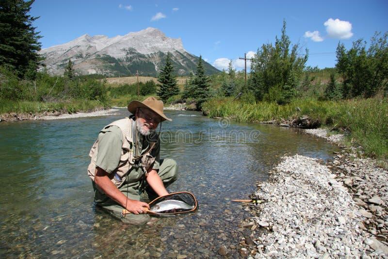 Fisher avec la truite photo stock