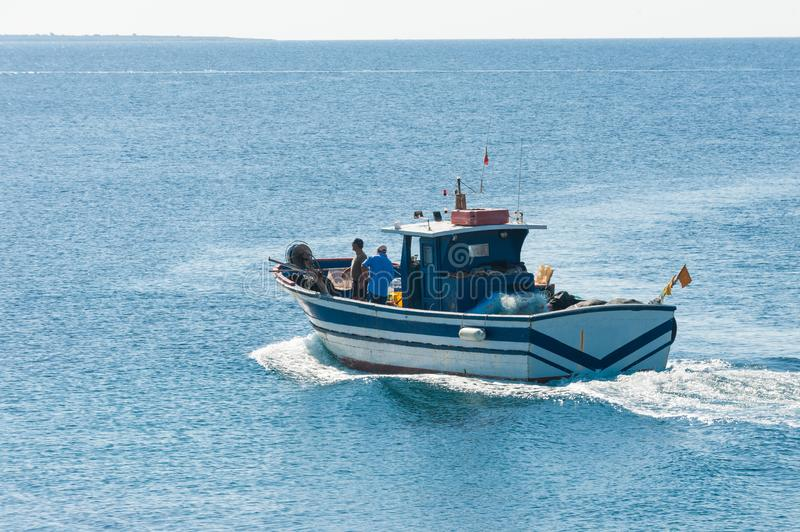 Fisher boat in action at sea stock photos