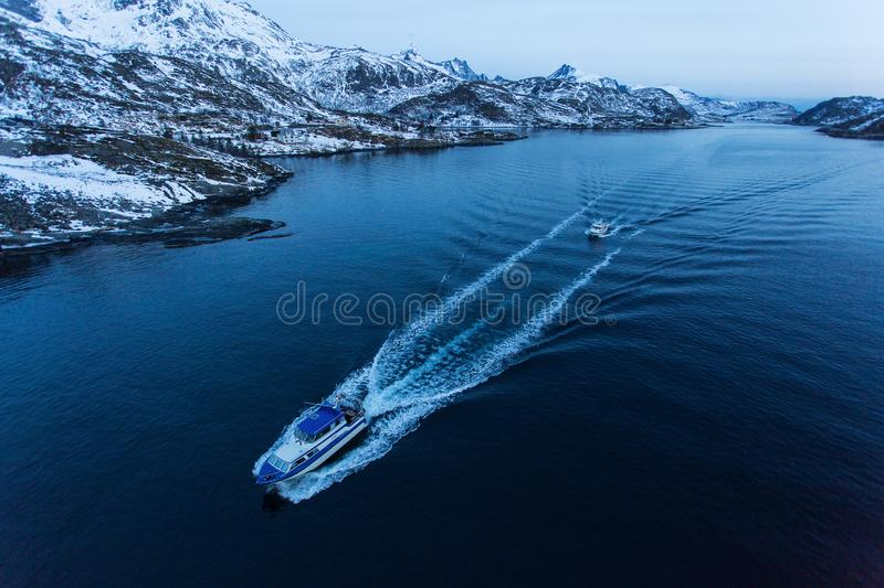Fisher boat going for fishing before sunrise with mountains full of snow in background. Lofoten Island, Norway stock images