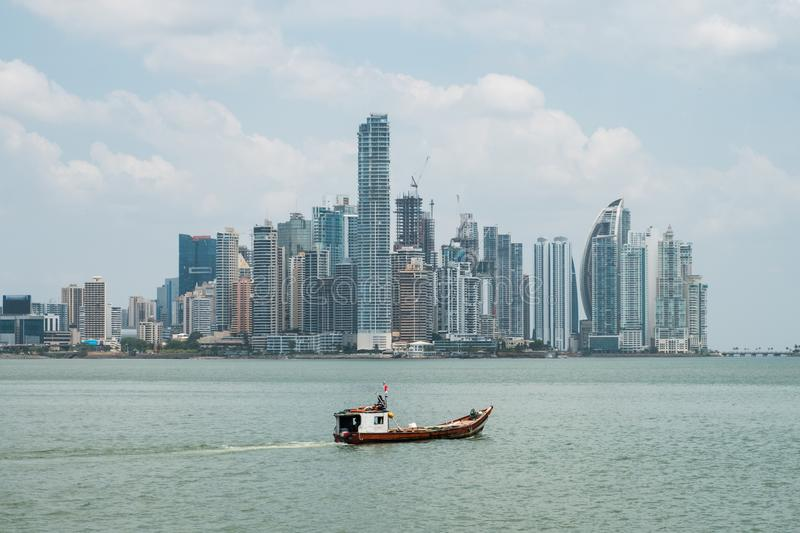 Fisher boat with modern skyscraper city skyline background - Pan stock photos