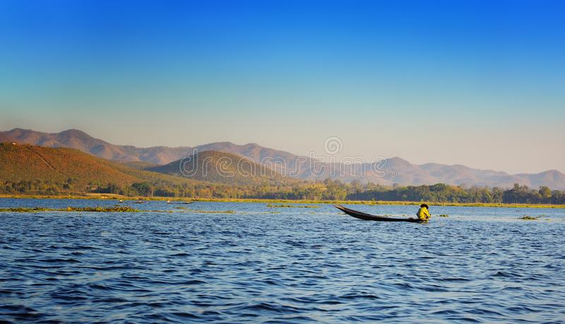 Fisher with a cap on a boat in a Myanmar water body. Landscape stock photo