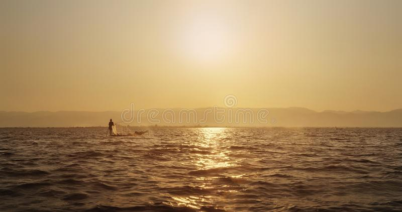 Fisher with a cap on a boat in a Myanmar water body in a sunset. Landscape stock image