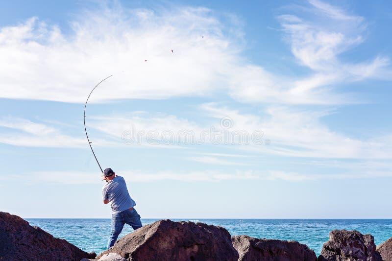 Fisher Casting His Rod Off Marina Breakwater Rocks foto de archivo