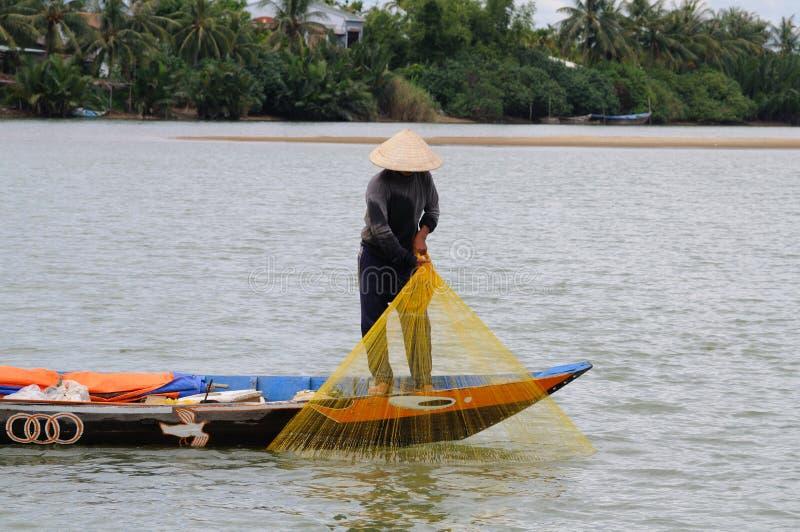Fisher, der sein Netz mit seinem Fang hochzieht lizenzfreies stockbild