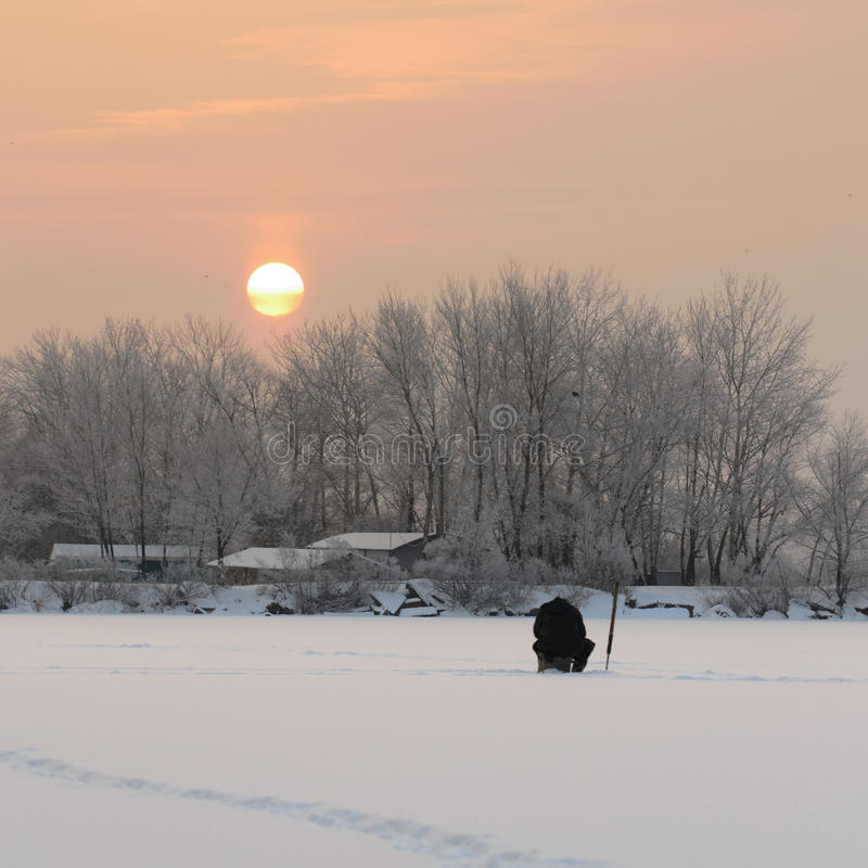 Fisher. Man at sunrise on the winter ice fishing on the river royalty free stock photos