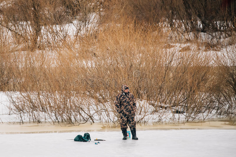 Fisher On Frozen River At Late Winter. Winter Ice Fishing Is Popular Hobby Among Belarusians Men. Rogachev, Belarus - February 25, 2017: Fisher On Frozen River royalty free stock photos