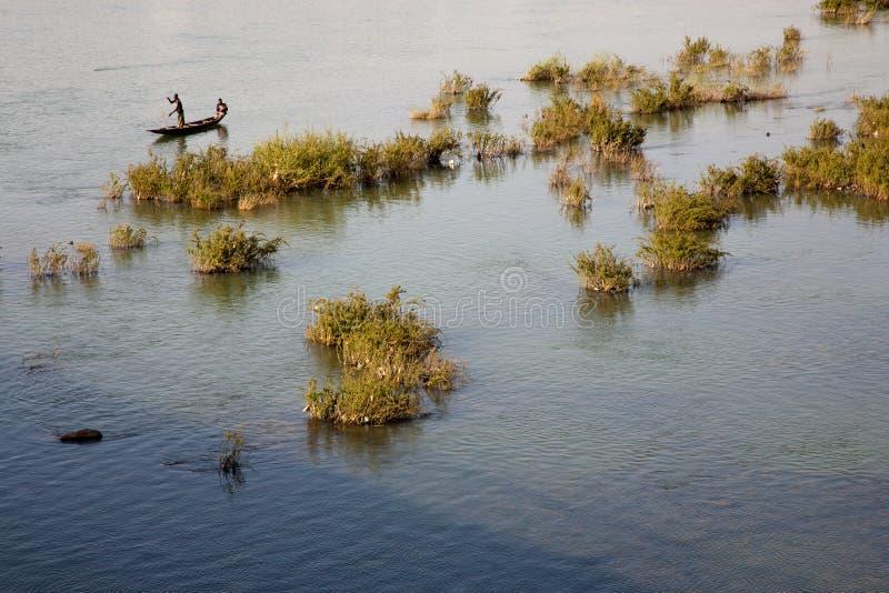 Fisher mężczyzna pracuje w ich łodzi na Niger rzece zdjęcia royalty free