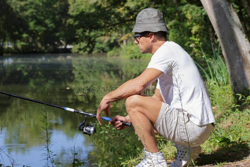 Fisher man fishing at lakeside. Man stock image
