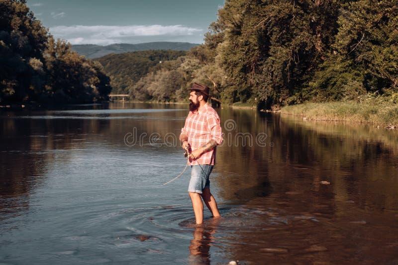 Fisher man som fiskar med snurrrullen Flyga stången och rullen med en brun forell från en ström Fiska i floden royaltyfri fotografi