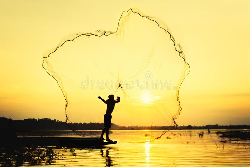 Silhouette fisher man throwing dip net fishing at lake with mountain and sunset sky. Background stock photo
