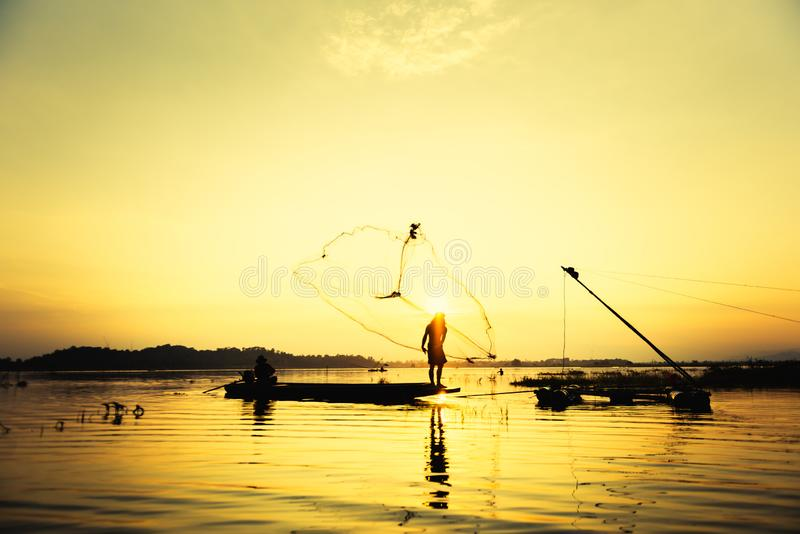 Silhouette fisher man throwing dip net fishing at lake with mountain and sunset sky. Background stock photos