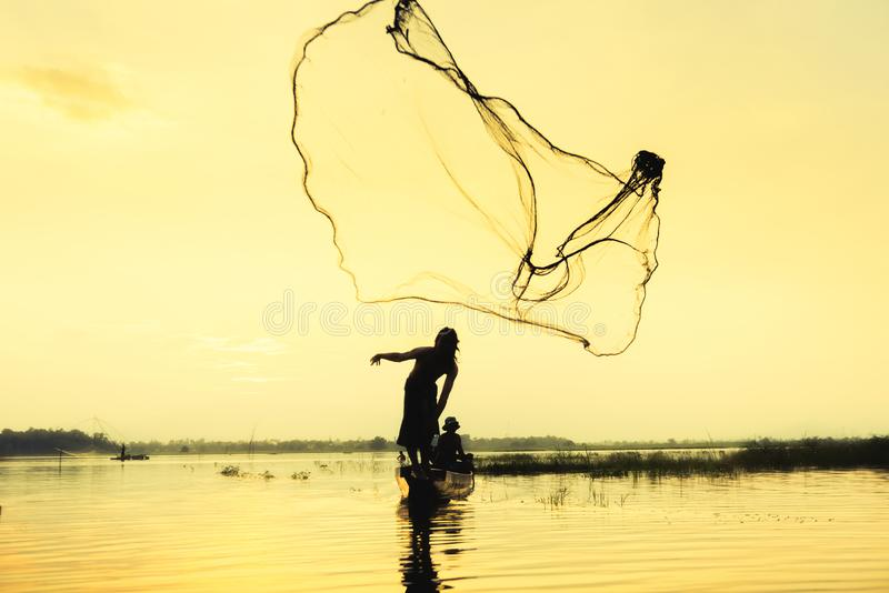 Silhouette fisher man throwing dip net fishing at lake with mountain and sunset sky. Background royalty free stock images