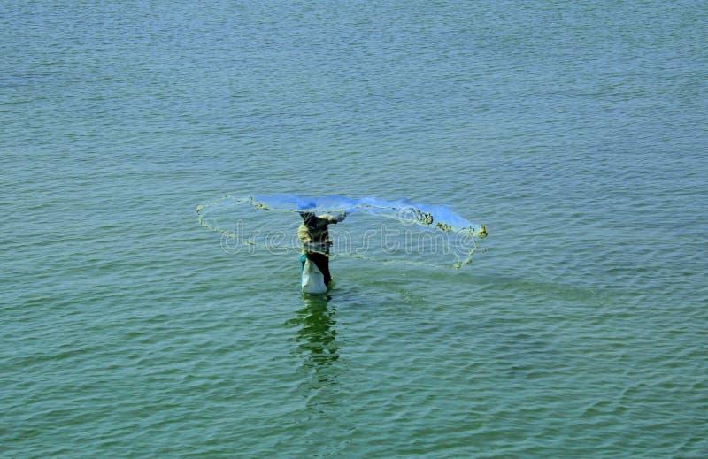 Fisher mankast ett netto på havsavkroken arkivfoton