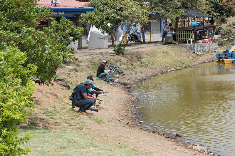 Fisher na costa do lago no parque de Sabana do La em San Jose, Costa Rica fotos de stock