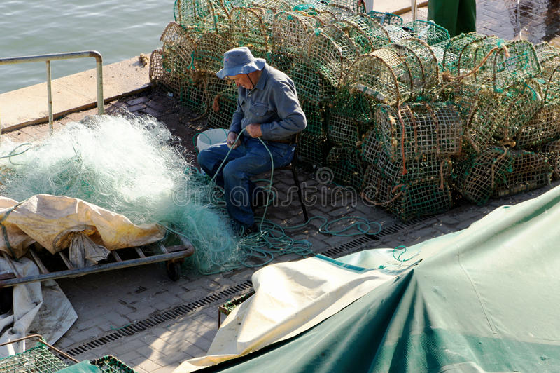 Fisher przymocowywa sieć rybacką obrazy royalty free
