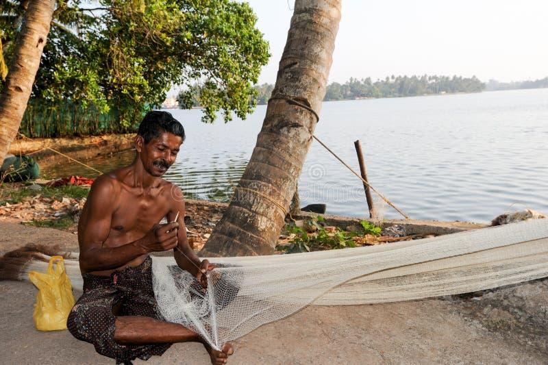 Fisher som reparerar hans fisknät royaltyfri bild