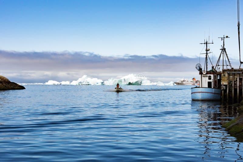 Fisherboats en cruisevoering voor ijsbergen lichtblauwe Noordpooloceaan, Groenland stock fotografie