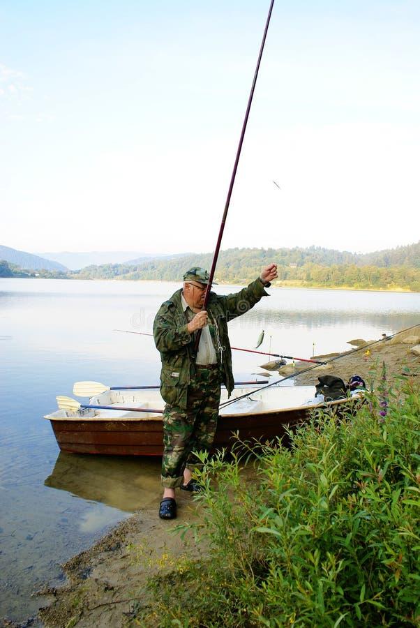 Fisherman. Elderly fisherman fishing at the lakeside stock images