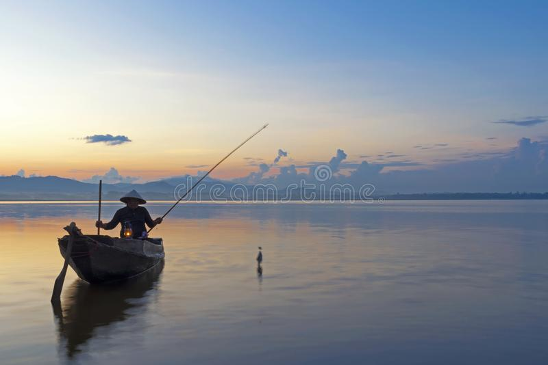 Fisherman action when fishing on lake in the sunshine morning and silhouette fisherman on the boat, royalty free stock images