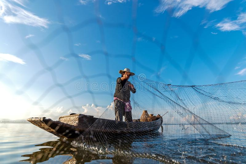 Fisherman action when fishing net  on lake in the sunshine morning outdoors on the boat. Agriculture Industry, royalty free stock photos