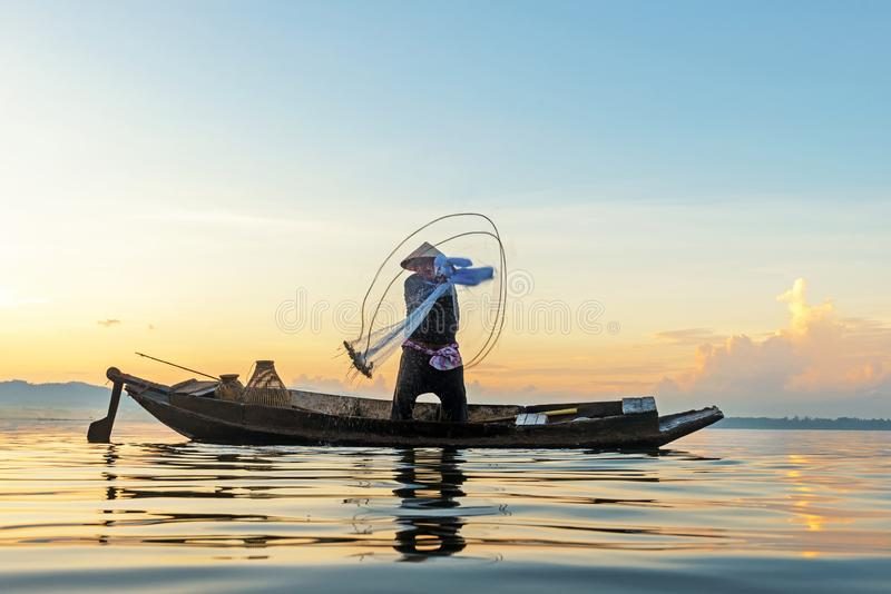 Fisherman action when fishing net  on lake in the sunshine morning outdoors on the boat. Agriculture Industry, stock photography