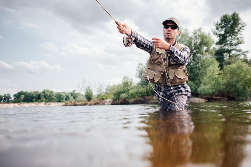 Fisherman in action. Guy is throwing spoon of fly rod in water and holding part of it in hand. He looks straight forward. Man wears special protection clothes stock photo