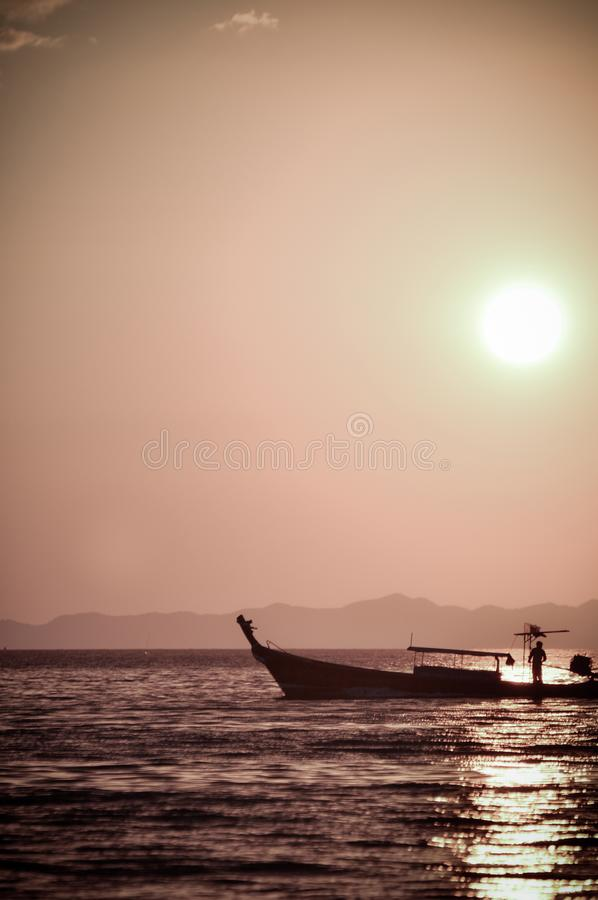 Fisherman in Ao Nang, Thailand. Sunset on a beach of ao nang stock photography