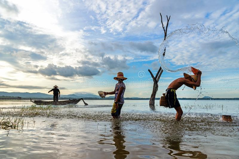Fisherman with asian boy and girl action when fishing net playing outdoor on river and lake in the morning sunrise. stock photography