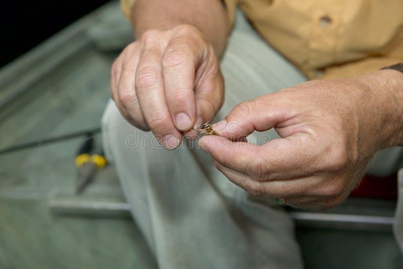 Fisherman baiting his hook stock photos