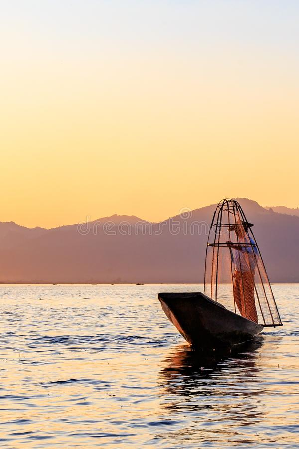 Fisherman on bamboo boat is catching fish by traditional handmade net. Photo made on Inle lake, Myanmar Burma stock photos