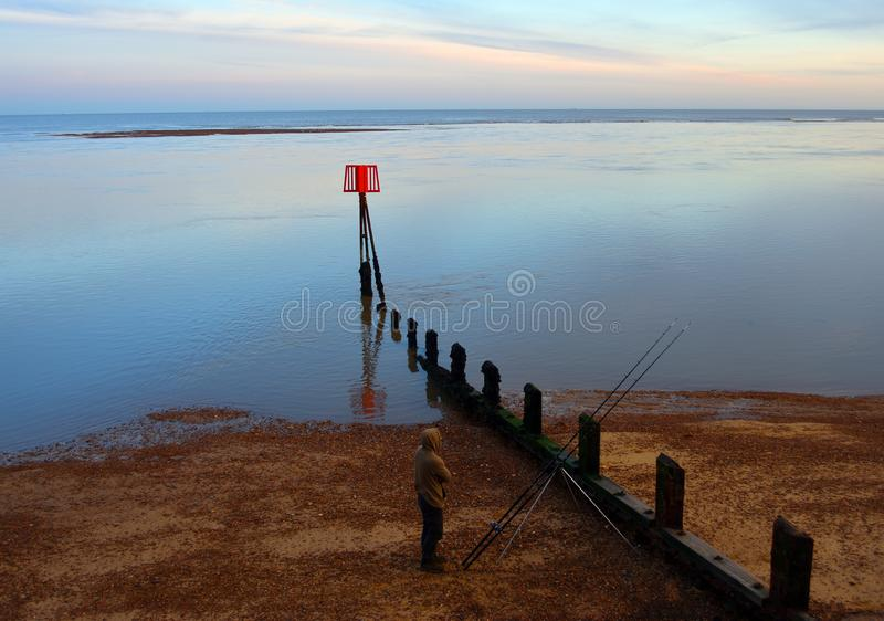Fisherman on the beach at twilght calm refective sea. stock image