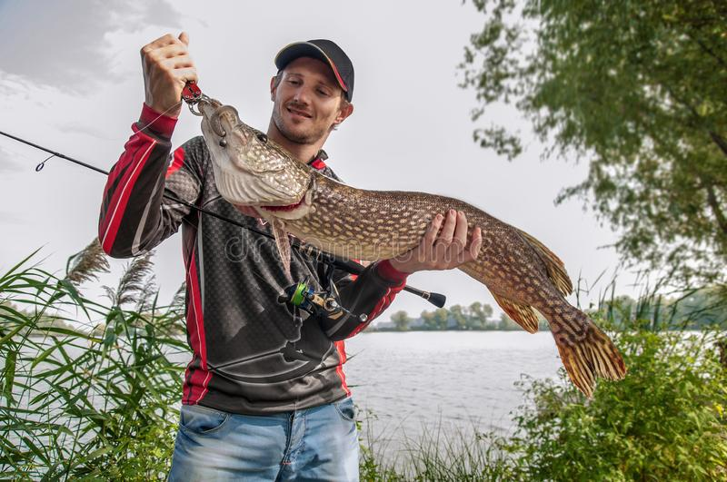 Fisherman with big pike fish trophy in hand on the lake background stock image