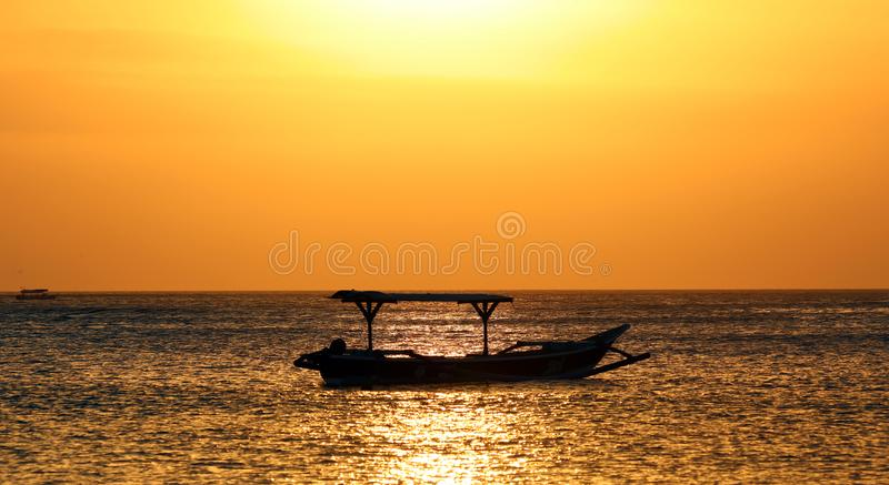 Fisherman boat in Bali, Indonesia during golden sunset. Ocean and sky looking like gold. Unique moment captured by the camera stock image