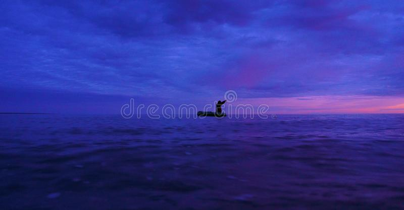 The fisherman in a boat fishing nets on sunset stock image