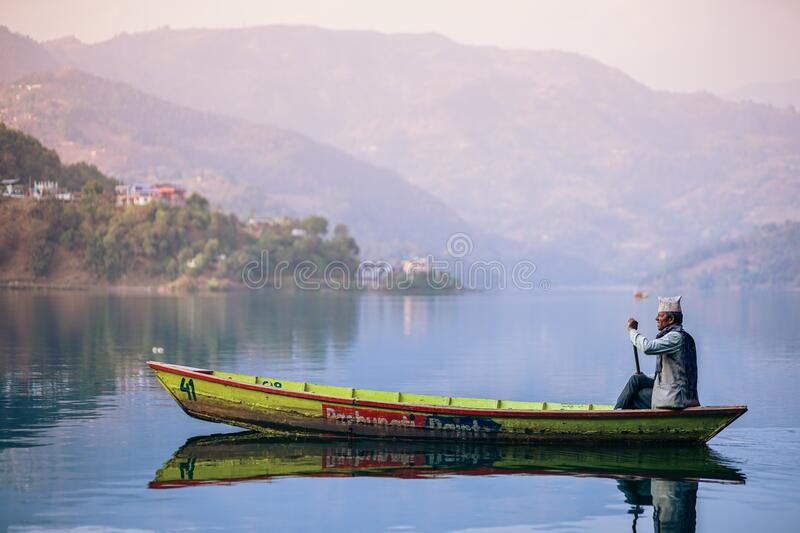 Fisherman in boat on lake royalty free stock photography