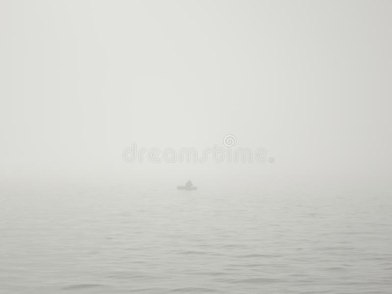 Fisherman in a boat on a lake in a thick fog catches fish with a fishing rod royalty free stock photo