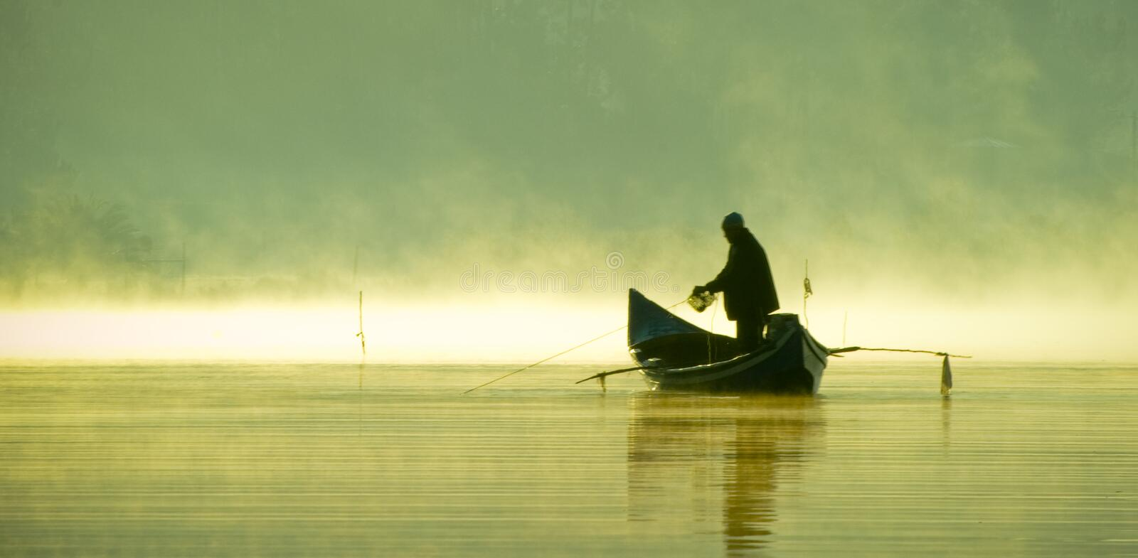 Fisherman on a boat silhouette royalty free stock photography