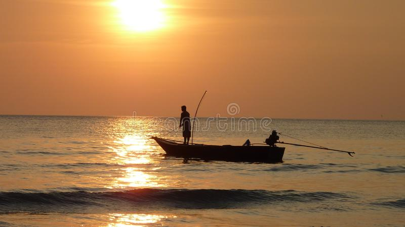 Fisherman in boat at sunset stock images