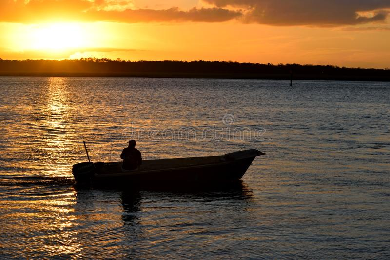 Fisherman in boat at sunset. Silhouette of a fisherman in a small boat in a body of water, returning from a day of fishing at sunset stock images