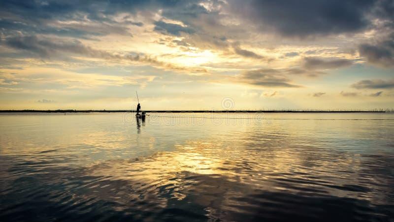 Fisherman on the boat use fishing nets at sunrise, Thailand stock images