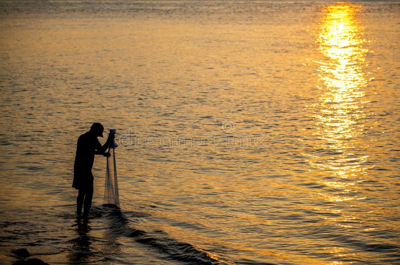 The fisherman cast a net the sea. In the morning, at sunrise, Songkhla province, Thailand country stock photography