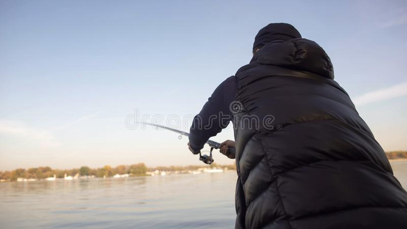 Fisherman casting spinning rod, tutorial for beginners, fishing gear, supplies royalty free stock images