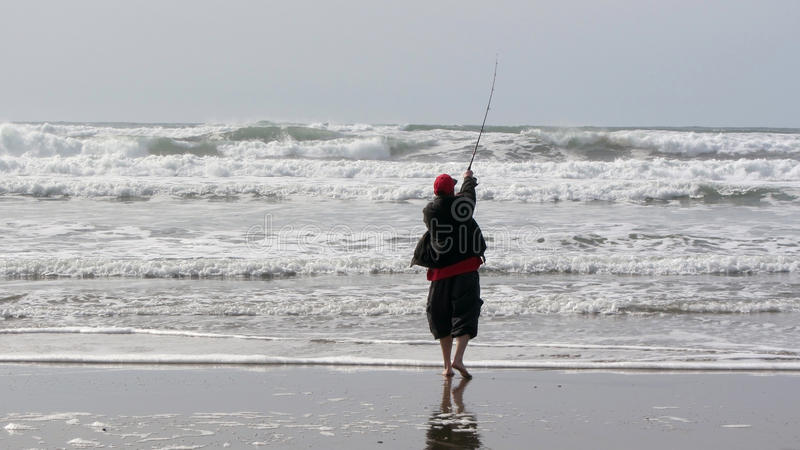 Fisherman casting into surf stock image