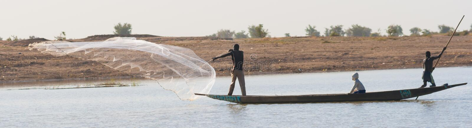 Fisherman casts a net on the Niger River, Mali. Djenné, Mali - December 28, 2009: Fisherman casts nets from pirogue, together with his two sons, on the Niger stock images