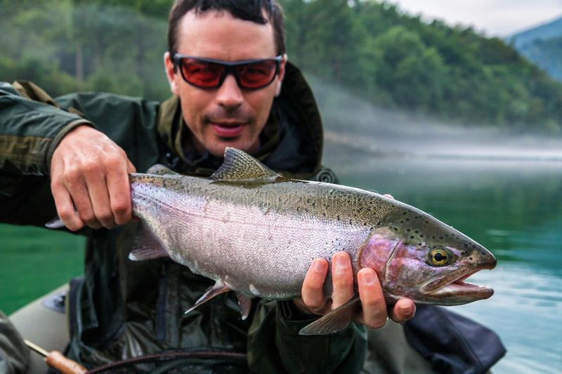 Fisherman with catch of Rainbow trout, Slovenia. Fisherman holding the catch of Rainbow trout Oncorhynchus mykiss on bellyboat, Jesenice, Slovenia. Fly fishing stock photos