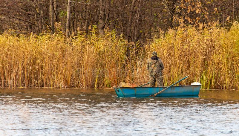 Fisherman catches from a boat on the pond in autumn royalty free stock image